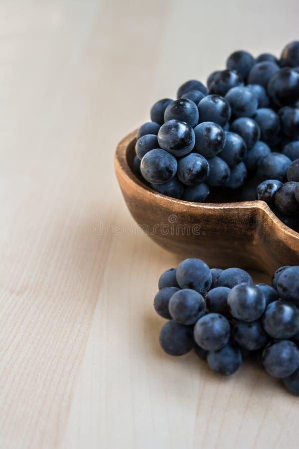 在心脏形状木板材的葡萄 免版税库存照片