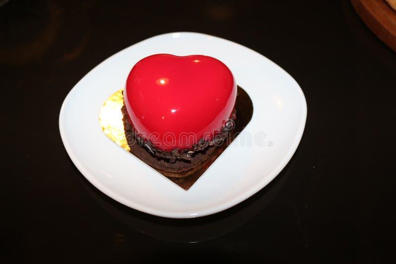 在心脏形状的乳酪蛋糕与在上面的红色釉 免版税图库摄影