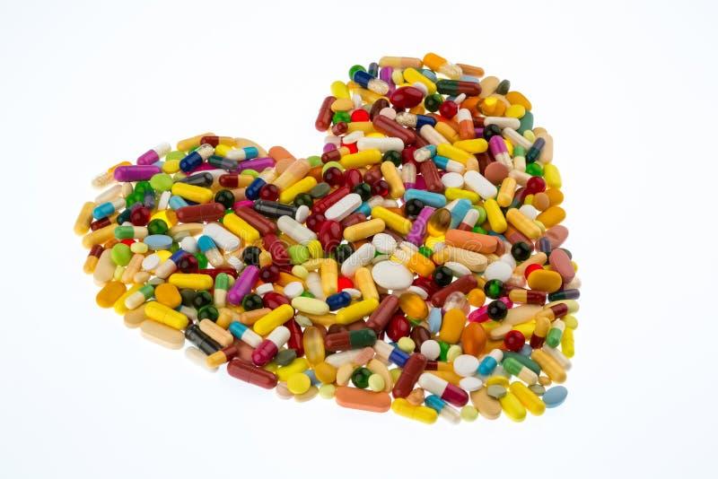在心脏形状的五颜六色的药片 免版税库存照片