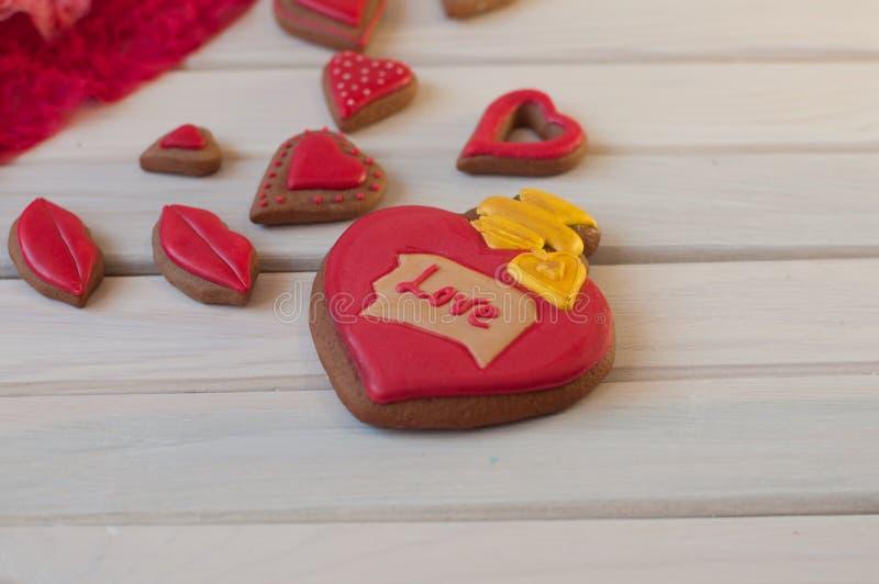 在心脏形状的几块给上釉的蜜糕,嘴唇在白色木背景说谎 免版税库存图片