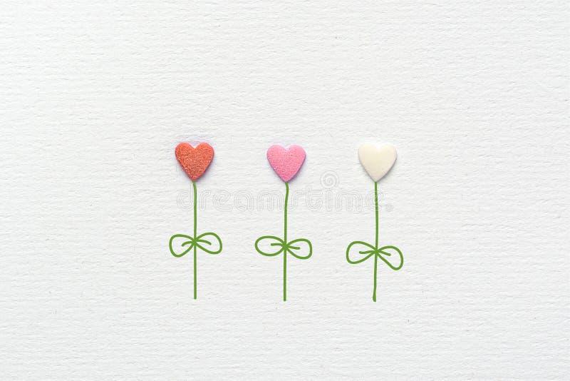 在心脏形状的多彩多姿的花由冰糖制成洒在白色水彩纸的手拉的蒸汽叶子 免版税库存照片