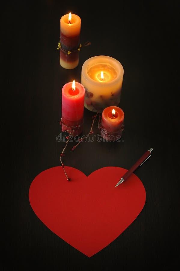 在心脏形状的情书与蜡烛和笔的 图库摄影