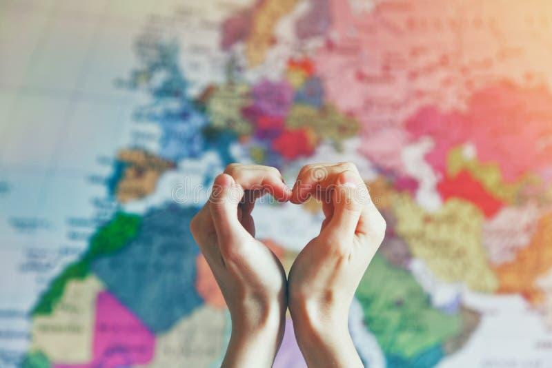 在心脏形状的手充满在世界地图的爱 库存照片