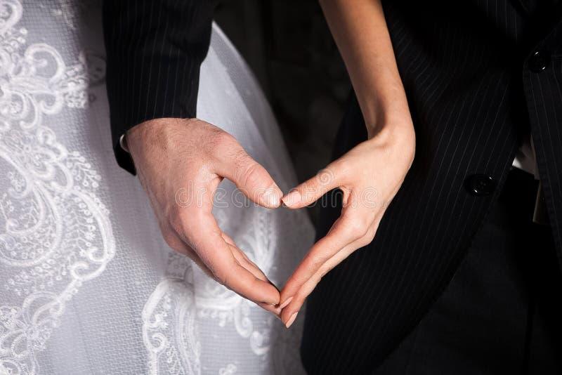 在心脏形状的新娘和新郎的手  免版税库存照片