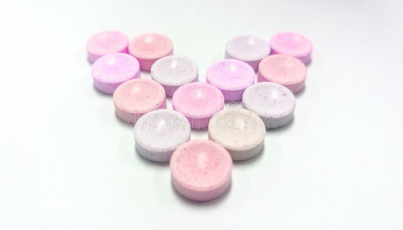 在心脏形状的桃红色糖果在白色背景,爱背景的 库存照片