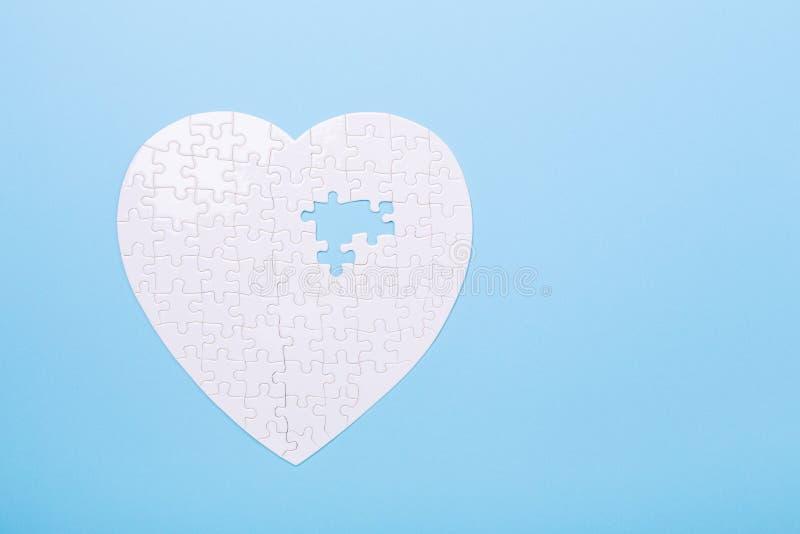在心脏形状的白色难题在蓝色心脏疾患药片的背景曲线锯的概念治疗的 库存照片