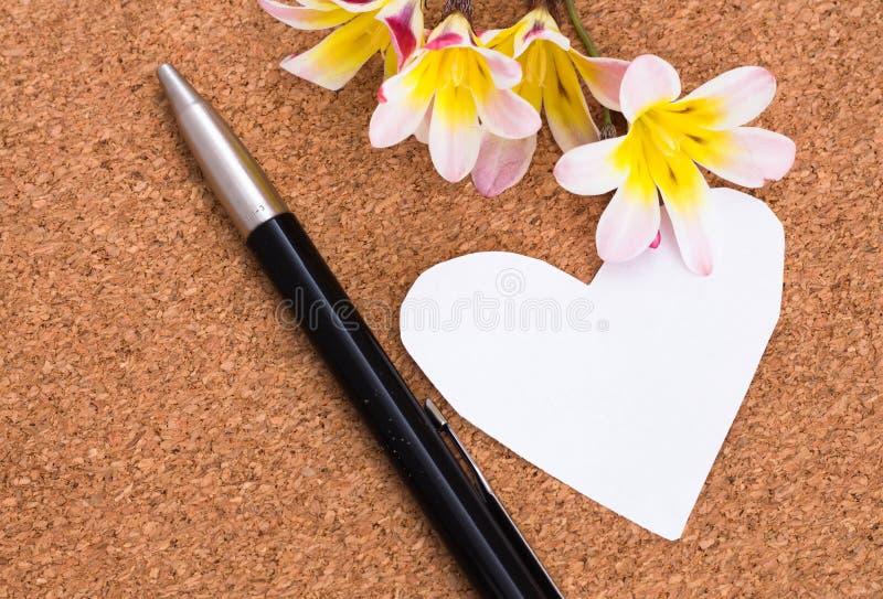 在心脏形状的空白的笔记与拷贝sapce和花的 免版税库存照片