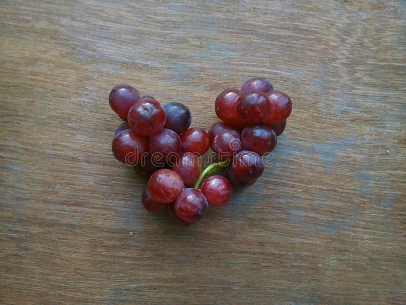 在心脏形状的红葡萄 免版税库存图片