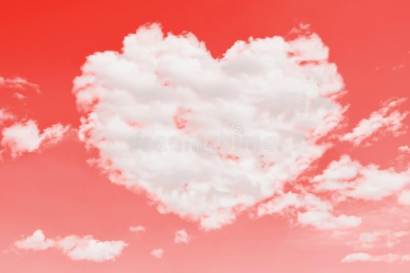 在心脏形状的美丽的云彩在珊瑚颜色背景的 免版税图库摄影