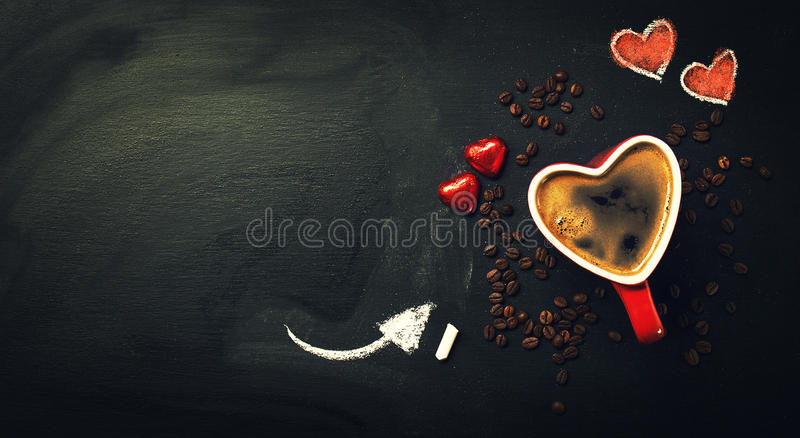在心脏形状红色杯的鲜美咖啡浓咖啡在黑板 免版税库存图片