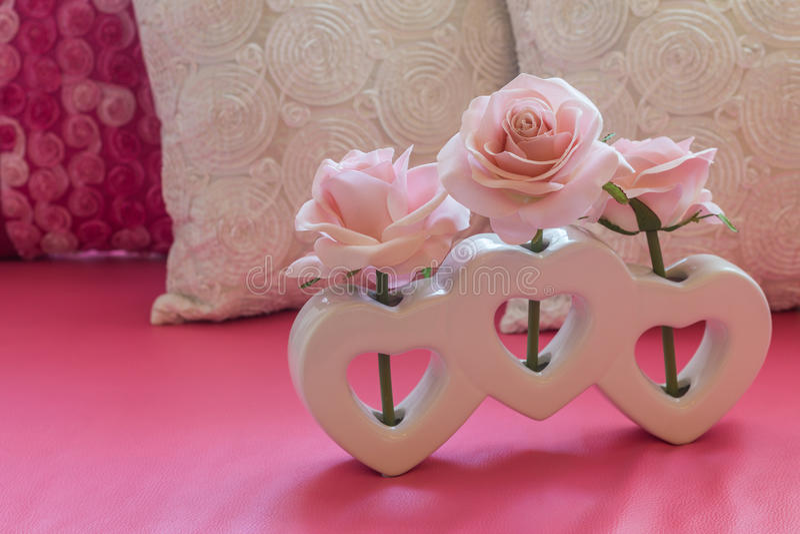 在心脏形状花瓶的人为桃红色玫瑰花 免版税库存图片