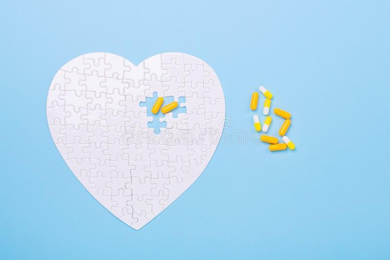 在心脏白色和黄色药片形状的难题在蓝色心脏疾患药片的背景曲线锯的概念治疗的 免版税库存照片