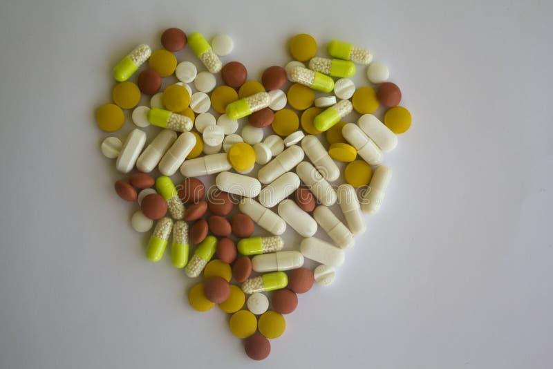在心脏的形状的五颜六色的药片 免版税库存照片