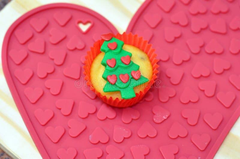在心脏盛肉盘的圣诞树杯形蛋糕 免版税图库摄影