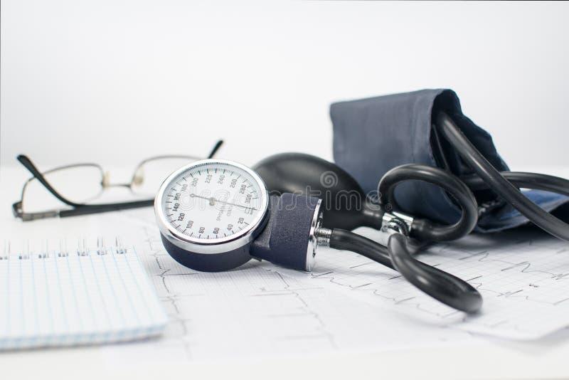 在心脏科医师Tonometer,心电图和笔记薄的工作表上的血压计纪录的 库存图片