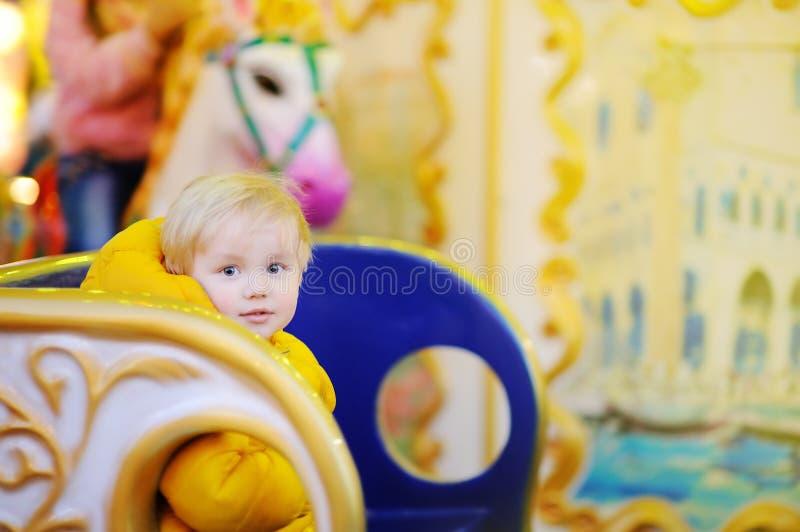 在快活五颜六色的转盘的小孩骑马去回合 图库摄影