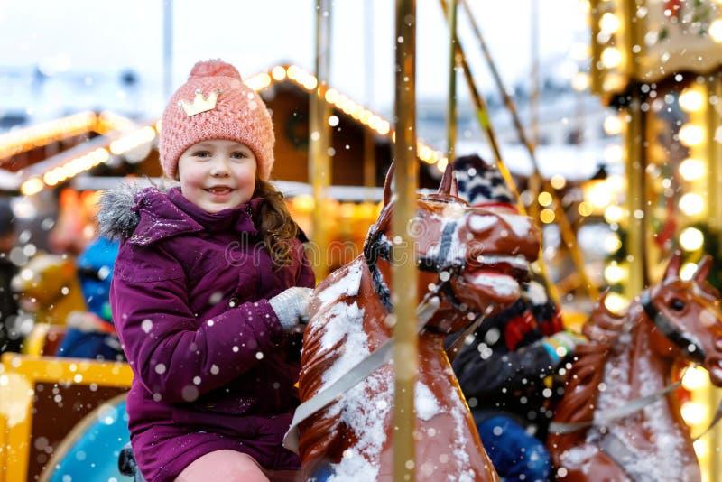 在快活的可爱的小孩女孩骑马努力去做回合转盘马在圣诞节游艺集市或市场,户外 愉快的子项 免版税图库摄影