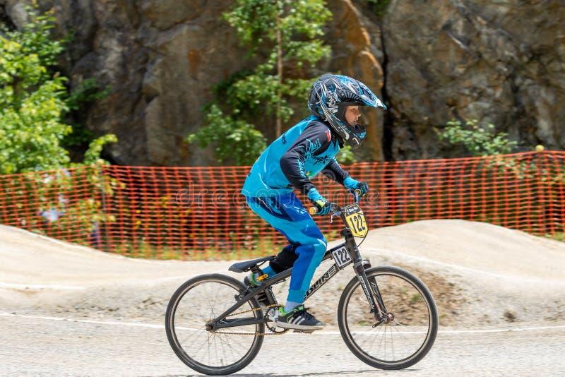 在快速驾驶的年轻男孩骑自行车者车手 免版税库存照片
