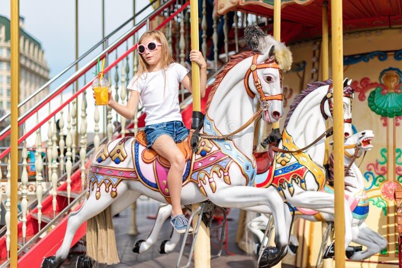 在快活的女孩骑马去回合 使用在转盘、夏天乐趣、愉快的童年和假期概念的小女孩 库存照片