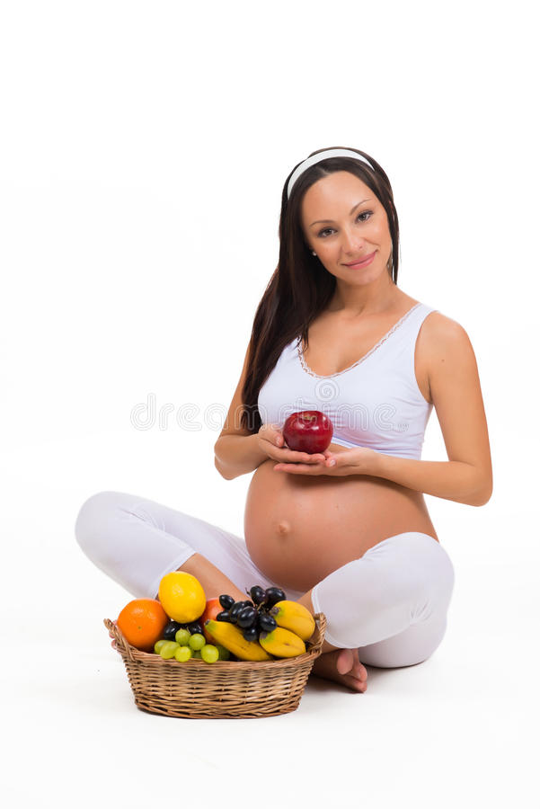 在怀孕期间的适当的营养 维生素和果子 吃苹果的孕妇 库存照片