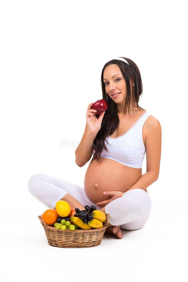 在怀孕期间的适当的营养 维生素和果子 吃苹果的孕妇 免版税图库摄影