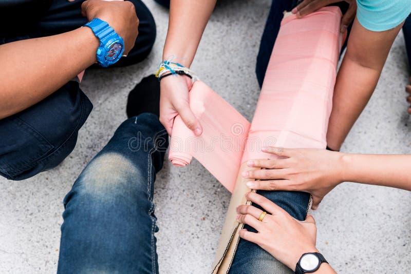 在急救训练教室,学生设法用夹板固定一个耐心` s断腿事件的腿与纸板和elast的 免版税库存照片