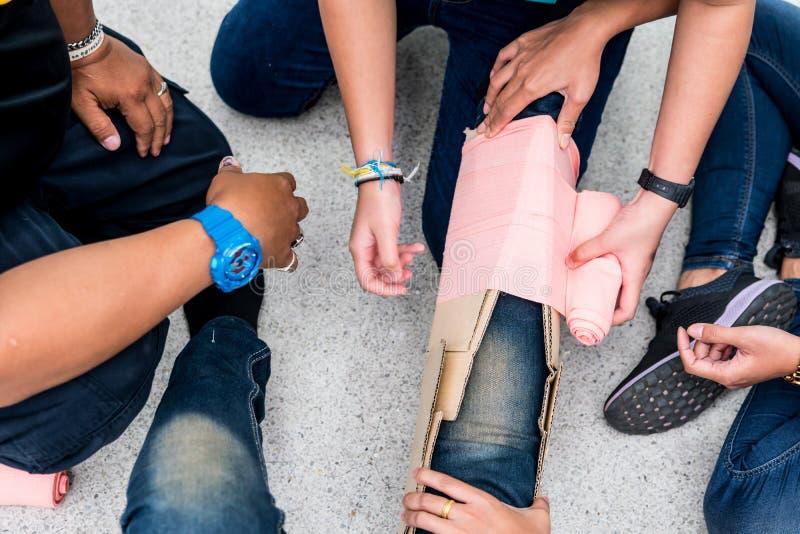 在急救训练教室,学生设法用夹板固定一个耐心` s断腿事件的腿与纸板和elast的 库存照片