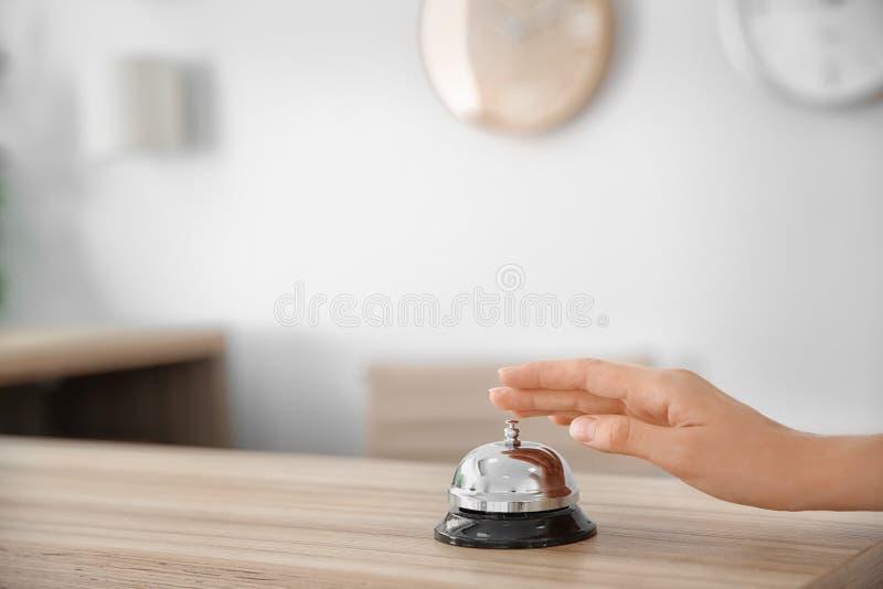 在总台上的妇女敲响的服务响铃 库存照片