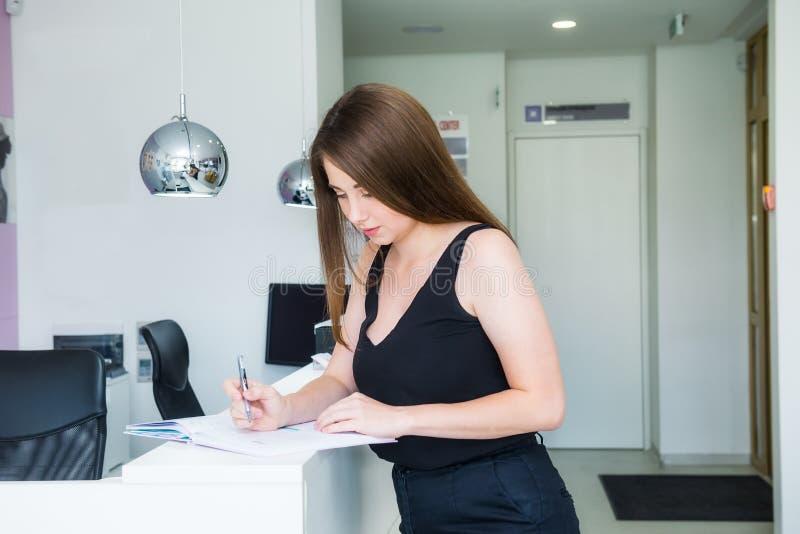 在总台的年轻女性经理身分在办公室大厅和计划日程里,在笔记本写,记录下来  库存图片