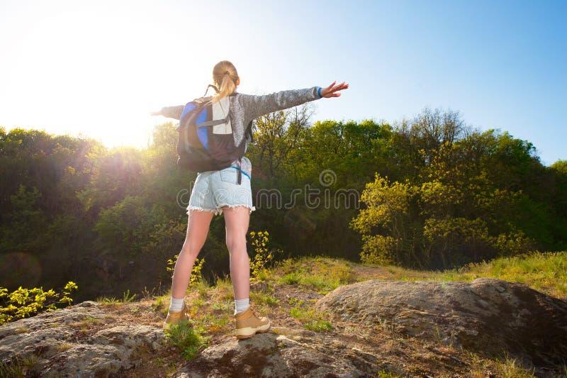 在总和期间,妇女背包徒步旅行者享受看法在道路的森林里 库存照片