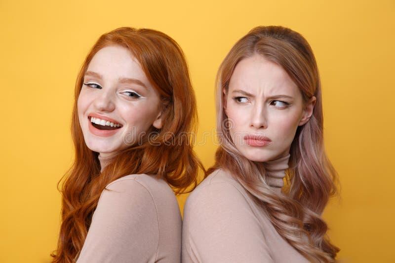 在恼怒的白肤金发的妇女附近的愉快的年轻红头发人夫人 免版税库存照片