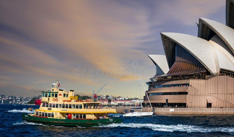 在悉尼歌剧院前面的轮渡和游艇航行在日落在悉尼,澳大利亚 免版税图库图片