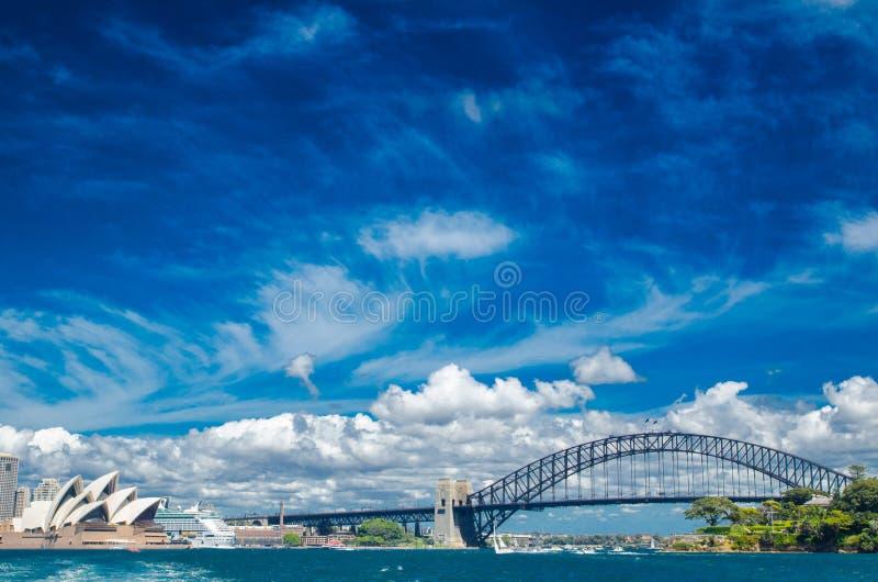在悉尼歌剧院和港口桥梁上的美好的剧烈的cloudscape有都市风景视图在阳光天 免版税图库摄影
