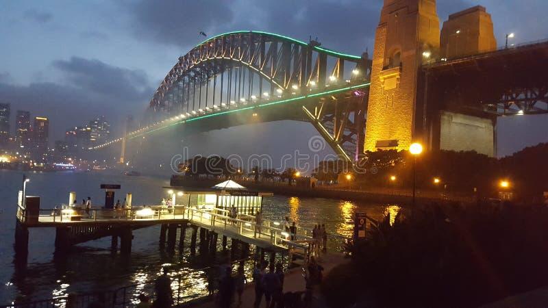 在悉尼港桥的微明在悉尼港口闪耀的和原始水在悉尼,NSW,澳大利亚 免版税图库摄影