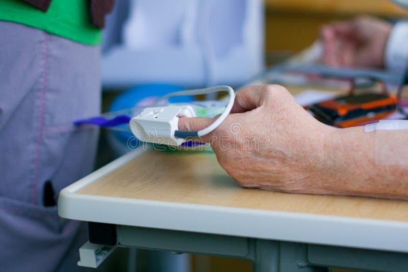 在患者的指尖的脉冲血氧定量计 免版税库存照片