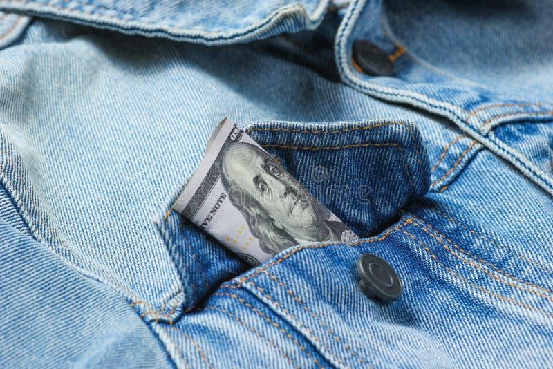 在您的牛仔裤夹克口袋特写镜头的一百美元票据,宏观照片 免版税库存图片