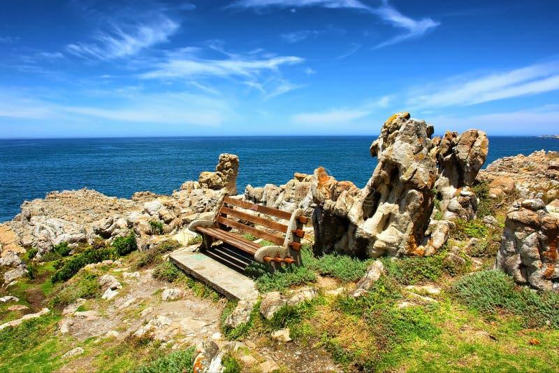 在惊人的岩层旁边的长凳 库存图片