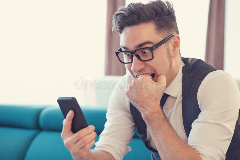 在惊吓的害怕的人观看的电话 免版税库存照片