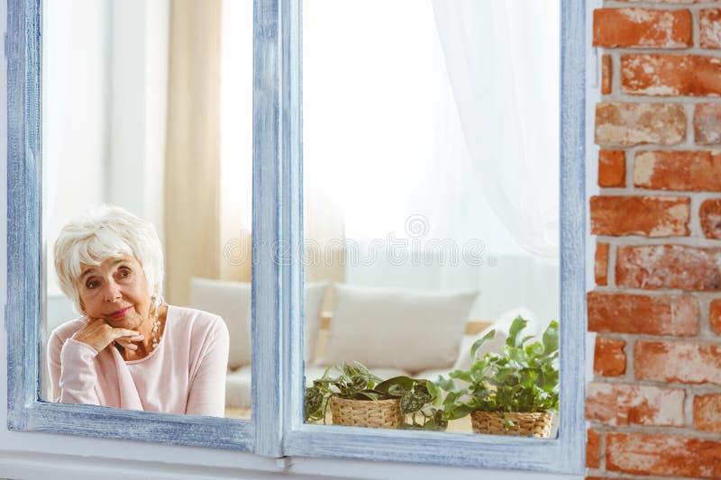 在想法失去的妇女由窗口 免版税图库摄影