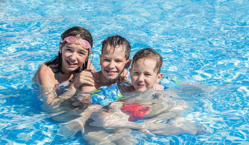 在愉快室外儿童的水池的两兄弟和姐姐游泳 库存照片