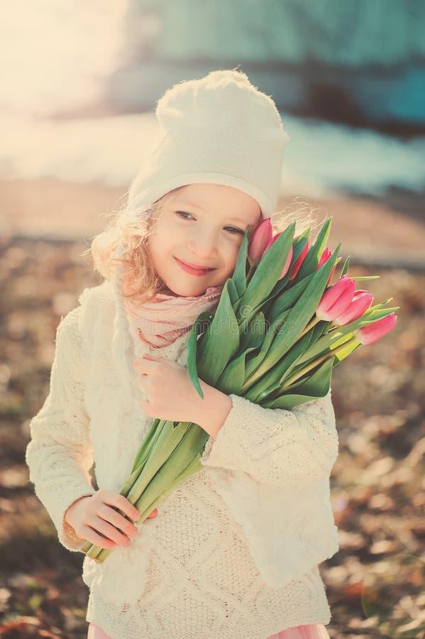 在愉快的儿童女孩淡色口气的春天画象有郁金香花束的为妇女的天 库存图片