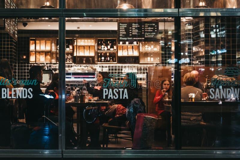 在意大利餐厅里面的人们在金丝雀码头,伦敦,英国,看法通过窗口从外面 图库摄影