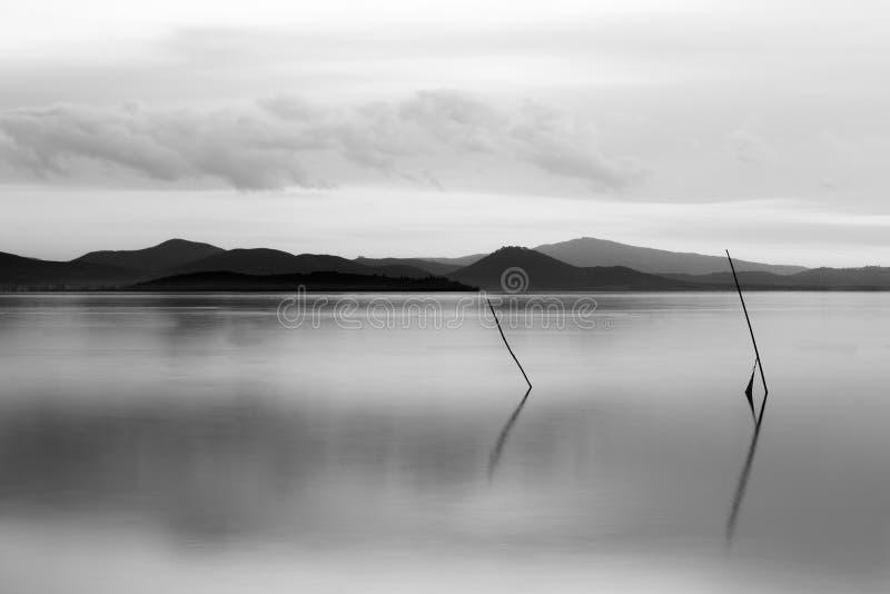 在意大利Trasimeno湖翁布里亚,黄昏时分,渔网杆在完美静止的水面上 库存照片
