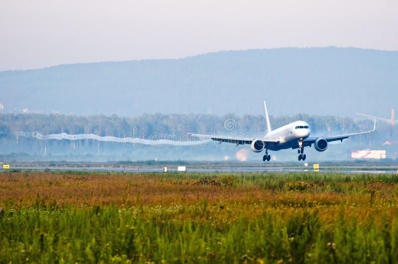 在感人的跑道着陆前的客机与来自翼梢的vortexes 免版税库存照片