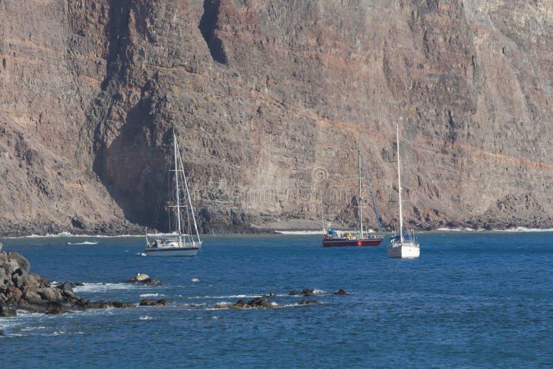 在戈梅拉岛下岩石的游艇  库存照片