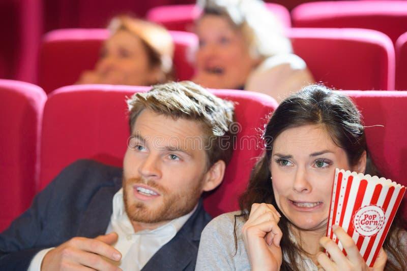 在戏院的害怕夫妇观看的影片 库存照片