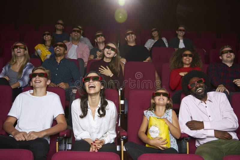 在戏院的观众戴3D眼镜观看喜剧影片的 免版税库存照片