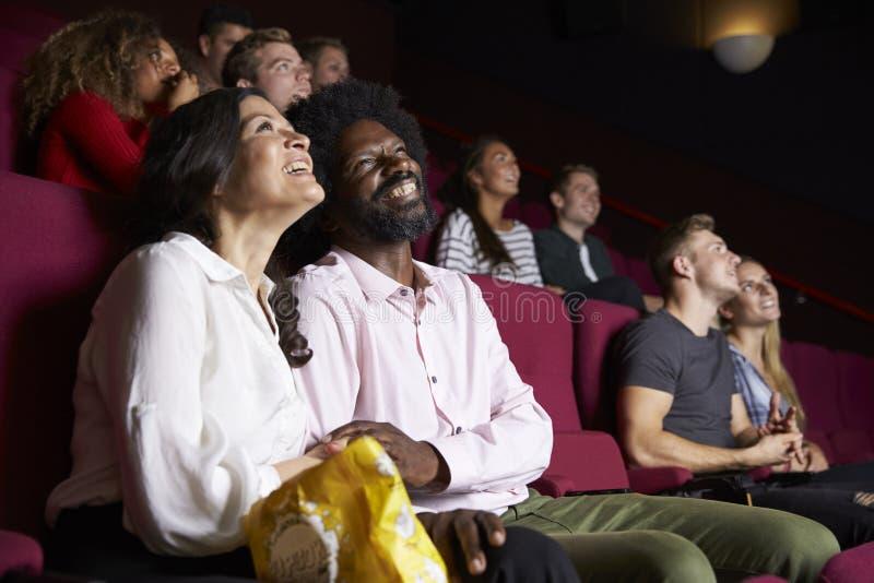 在戏院观看的喜剧影片的夫妇 免版税库存照片