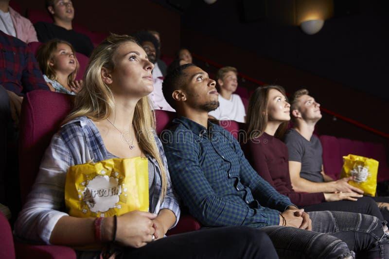 在戏院观看的影片和吃玉米花的年轻夫妇 图库摄影