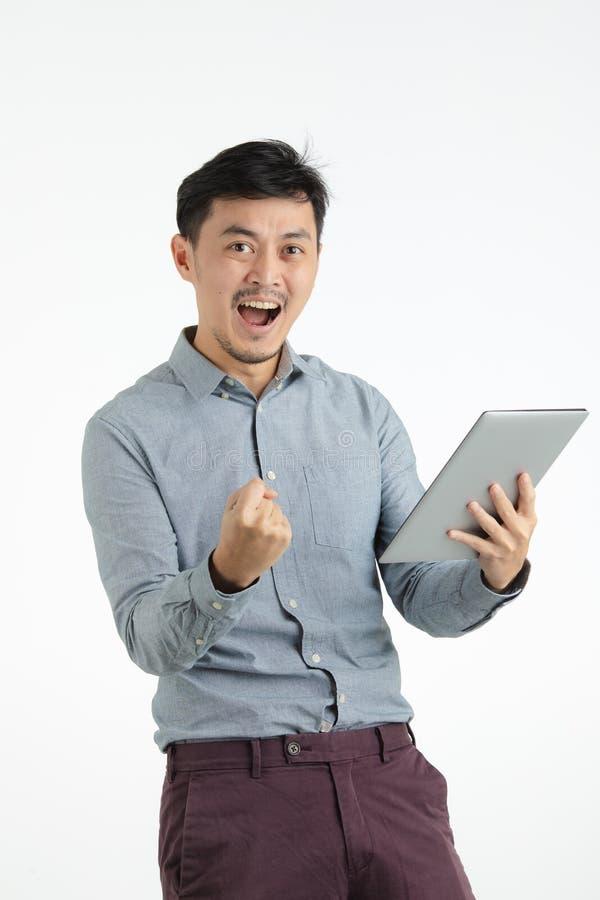 在成功惊叹的亚裔年轻人 免版税库存照片